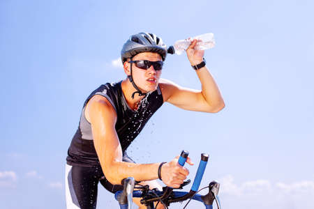 Triathlete cools his head while cycling on a bicycle