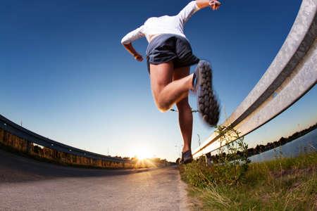 correr: Hombre que se ejecuta rápidamente en la carretera durante el atardecer.