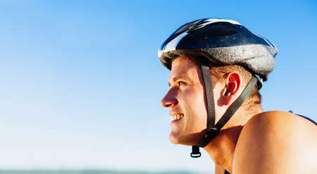 Young man biking with helmet on head Standard-Bild