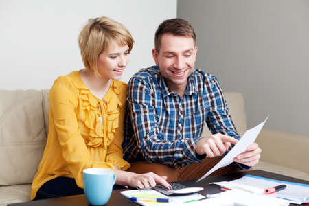Happy couple calculating bills sitting sonf sofa in living room Stockfoto