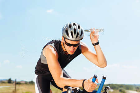 velo: Triathlete cools his head while cycling on a bicycle