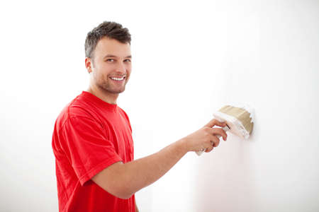 Young man painting wall with white paint. photo