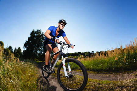Cyclist riding mountain bike on country road.