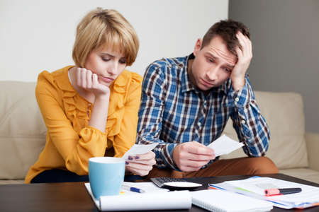 Sad, depressed young couple paying bills.