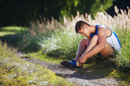 Broken ancle. Athlete sitting on the ground with injury.