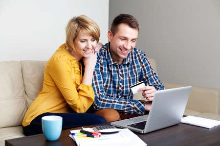 factura: joven pareja se paga con tarjeta de crédito para compras en línea Foto de archivo