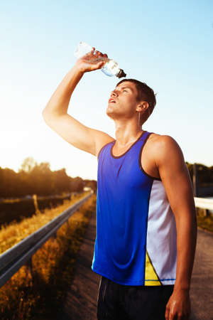 Athlete drinking after workout. Cross training. Health and fitness concept.