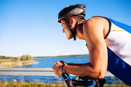 caucasian race: Happy triathlete cycling on a bicycle