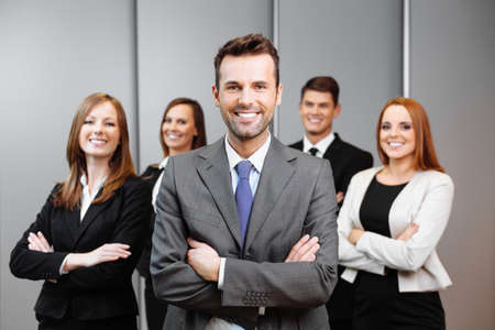 staff team: Team leader stands with coworkers in background