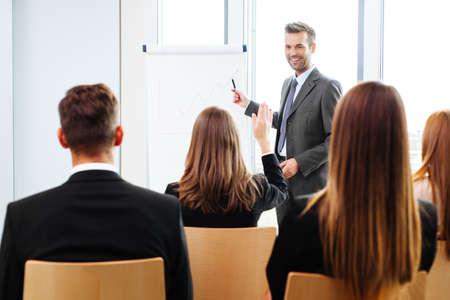preguntando: Hombre de negocios dando una presentación en el rotafolio. concepto del trabajo