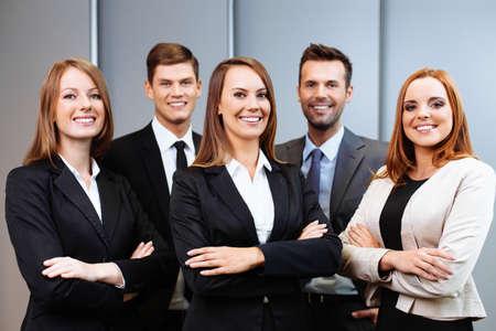 Überzeugte Geschäftsleute mit weiblicher Führer stehen