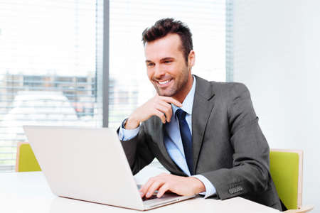 Happy businessman wbrowsing web on his laptop in the office