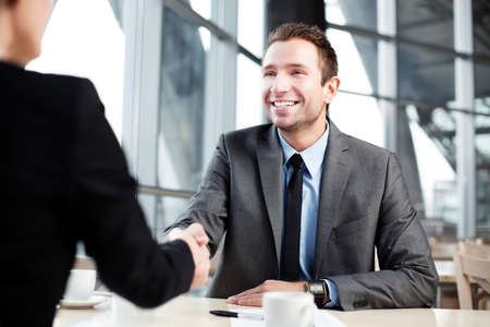 business relationship: Happy businessman shaking hand with businesswoman. Stock Photo