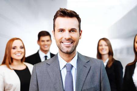 バック グラウンドでのビジネス人々 のグループで幸せなチーム リーダーの肖像画