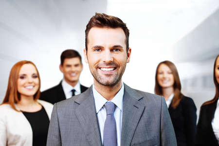 Portrait of happy team leader with group of business people in background