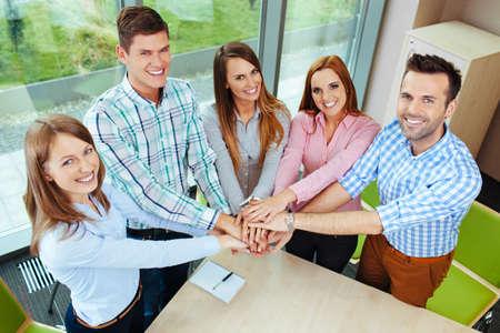 Groep gelukkige corporate mensen de handen ineen boven tafel