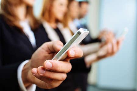 スマート フォンを使用して実業家のクローズ アップ。ビジネス コンセプト