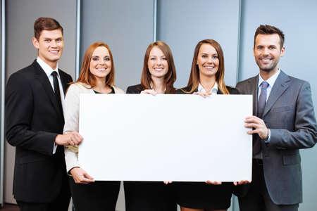 Gruppe Geschäftsleute, die Holdinganschlagtafel im Büro