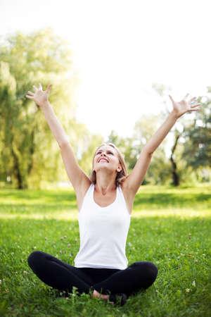 Glückliche junge Frau mit erhobenen Armen auf Gras zu sitzen photo