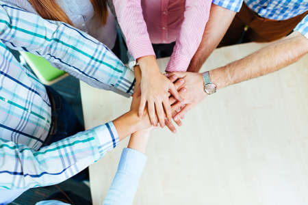 Group of corporate people working on new project joining hands over table