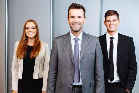personas de pie: Tres personas de negocios feliz permanente en la Oficina