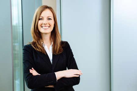 Überzeugte Geschäftsfrau steht im Büro Standard-Bild