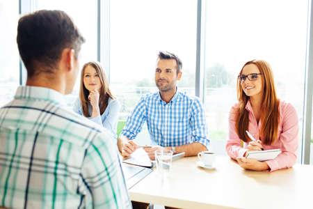 Rekrutierung. Drei Corporate Menschen Interview junger Mann