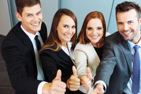 Grupo de empresarios exitosos que muestran los pulgares para arriba