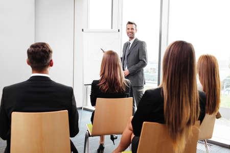 reunion de trabajo: Empresario de pie en el rotafolio que da una presentación para los empleados Foto de archivo