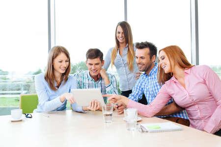 企業のオフィスでの会議と、テーブルに座ってのグループ