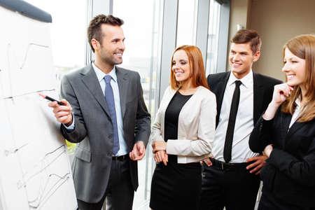 gestion empresarial: El hombre de negocios que da la presentación en el rotafolio. Reunión de negocios en la oficina