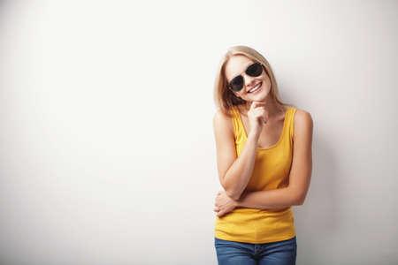 Junge Frau mit gelben T-Shirt und Sonnenbrille lächelnd. photo