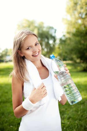 Trinkwasser der jungen Frau nach der Ausbildung photo