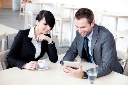 Business meeting. Businesswoman and businessman in restaurant, talking.