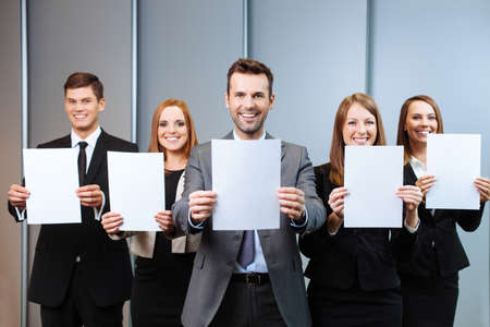 Business people holding blank paper cards