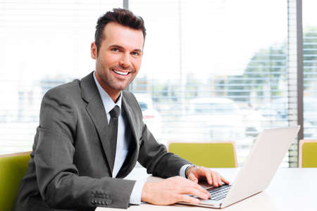 Happy businessman sit at desk in the office. Looking at camera, working with laptop