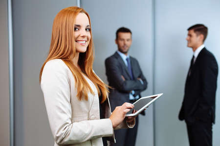 Beautiful business woman standing with digital tablet with business people in background
