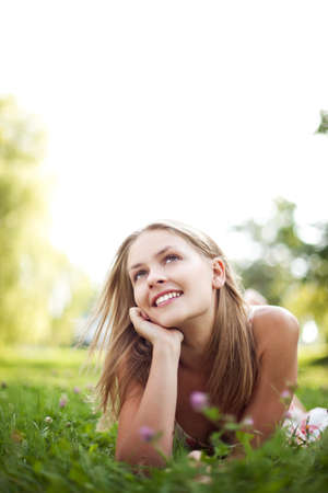 young woman smiling: Beautiful young woman lie on grass Stock Photo
