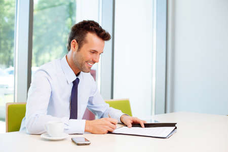 office documents: Happy man signing document in the office Stock Photo