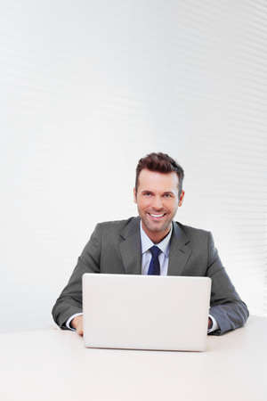 businessman suit: Happy businessman working on laptop in the office