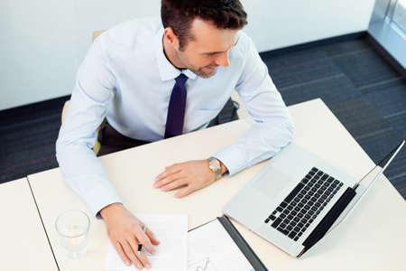Beschäftigter Mann im Büro arbeiten. Erhöhte Ansicht. Geschäftskonzept