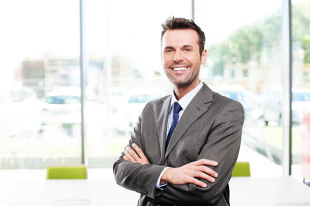 Happy businessman in the office standing with crossed arms Reklamní fotografie