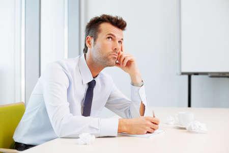 hombre pensando: hombre joven que piensa en nuevo plan de negocios.