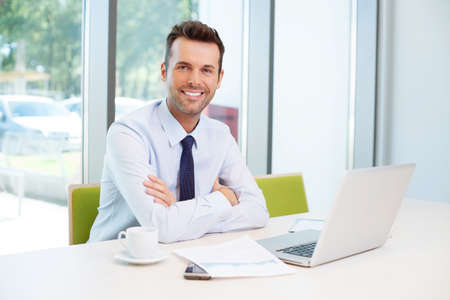 joyful businessman: Happy man sitting at desk in the office