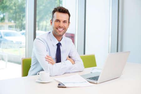 Szczęśliwy człowiek siedzi przy biurku w biurze
