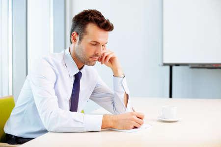 hombre pensando: Joven escribir en el cuaderno en la oficina