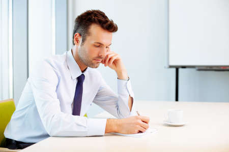 Young man writing on notebook in office