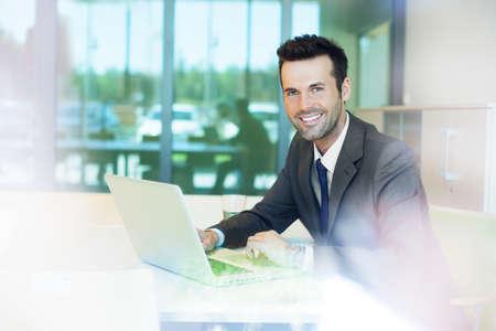 Handsome businessman working on laptop Foto de archivo