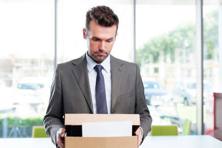 unemployed dismissed: Sad businessman leaving office after being fired Stock Photo