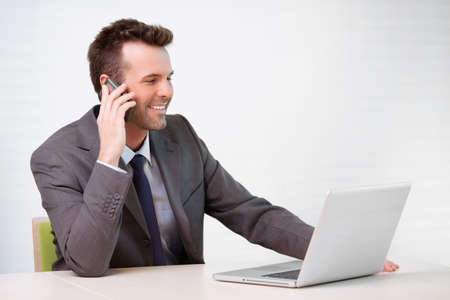 people on computers: Manager talking on the phone in the office Stock Photo